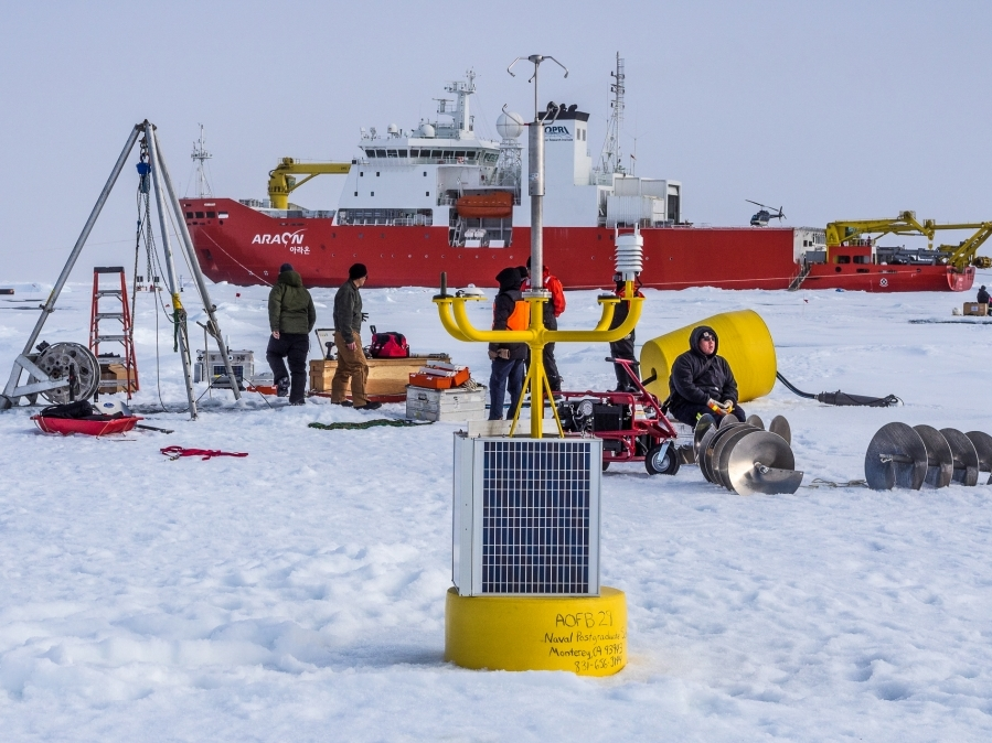 The central node of the MIZ array's northernmost cluster. Autonomous Ocean Flux Buoy (foreground) with an Ice Tethered Profiler being deployed behind. IBRV Araon in the background.