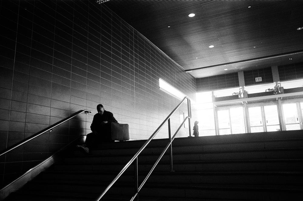 Man_sitting_backlit_staircase.jpg