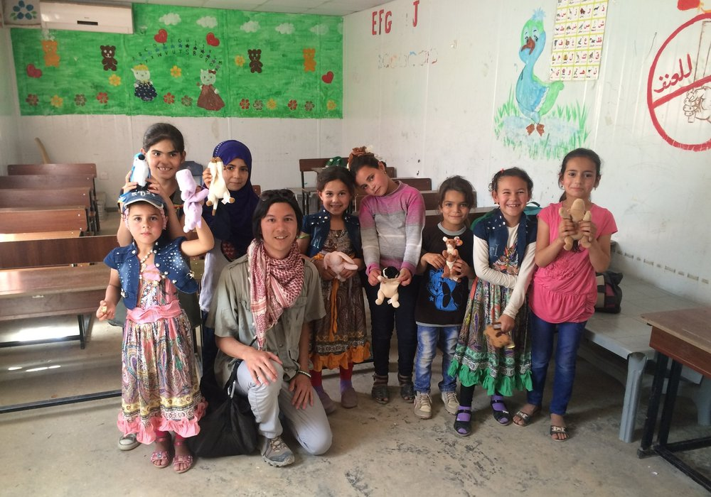 Team member Alex giving beanie babies to a classroom of girls at the Zaatari Refugee Camp in Jordan.