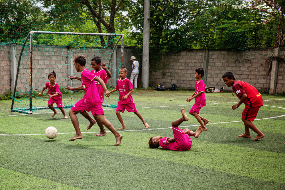 Most of the kids playing soccer are street children. They spend most their nights traveling through the streets high on glue.