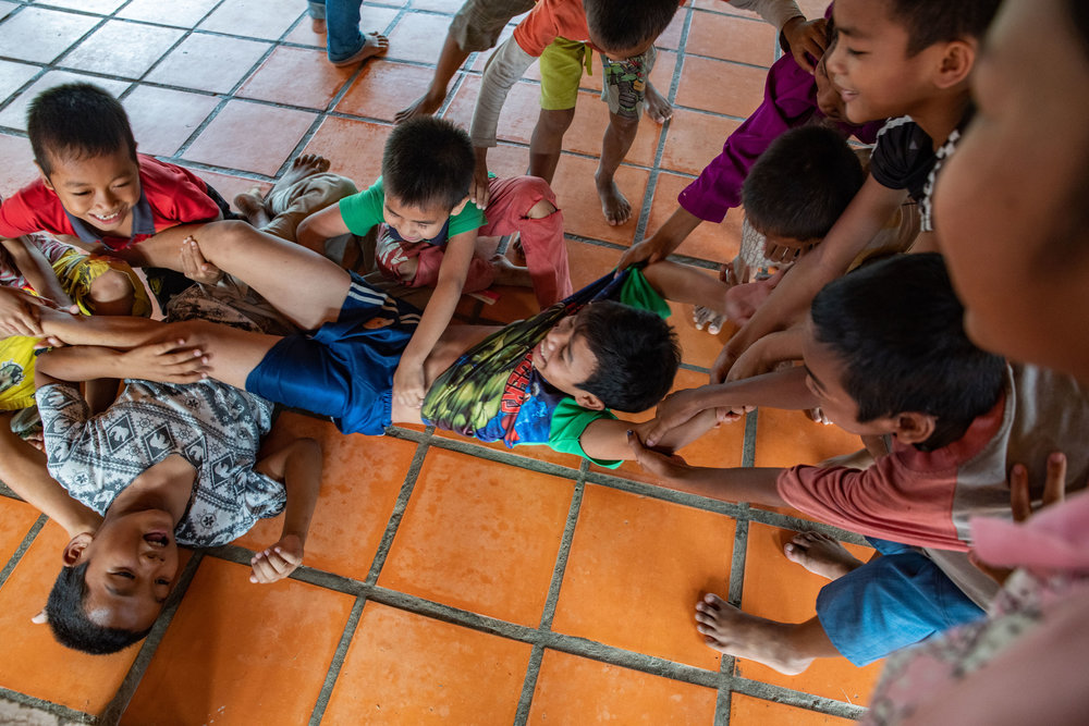 These kids love playing games together. Their common bond makes them a family.