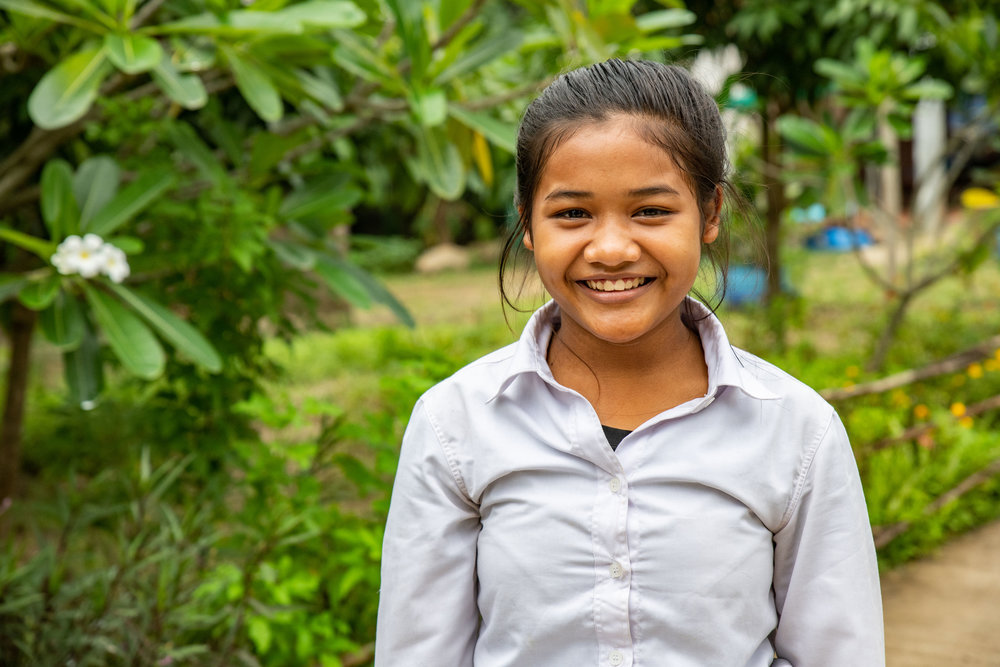 This is the bravest young girl I have ever met. At the age of 3 her older sister was sold to a Trafficker in Thailand by her mother. Two years later her mom sold her too. While working on the street she saw her sister. She went to her and told her… you are my sister. The other girl didn't believe her. She was finally able to convince her that they were sisters after naming their mother and father. This young girl knew that what they were doing was illegal and one day she snuck out to find her sister so that they could escape. She told her sister her plan. When the boss wasn't watching them they would sneak into the bathrooms and wait for someone to help them. Her sister was scared and didn't want to do it. Even though she wanted to escape with her sister she knew she wouldn't be able to. So as her boss wasn't watching she snuck into the bathroom. A few hours later a Thai cleaning woman came into the bathroom. This young girl had to trust this woman. So she tried to get the woman to understand that she was trafficked. Even with a language barrier somehow the woman understood. She hid the young girl in the bathroom and then when it was time she was able to bring her to the Thai border patrol. This young girl told the police everything about the man who had trafficked her and they were able to arrest him and his associates. She was then brought to Damnok Toek and has been here ever since. She wants to be a teacher when she grows up.