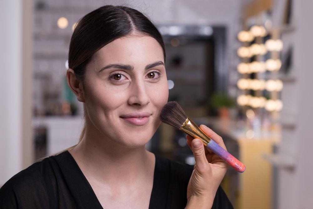 STEP 6 - Anschließend wird das Make-up mit Puder fixiert. So wird es haltbar und es können weitere pudrige Produkte folgen. Damit sich der Puder wirklich mit der Foundation verbindet, wird das Produkt mit einem großen Pinsel und weichem Druck gleichmäßig eingearbeitet.