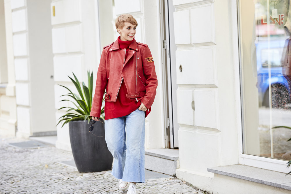 Der rote Pullover und die rote Lederjacke sind aus dem Laden von Ofelia Berlin