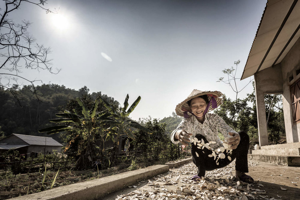 A woman spreads dry products | Habitat for Humanity | Southeast Asia NGO Photographer | Francis Roux