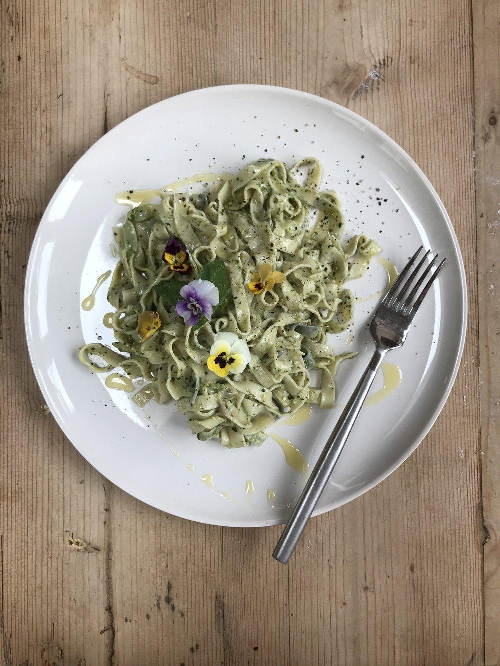 Fresh pasta, fresh pesto with edible flowers