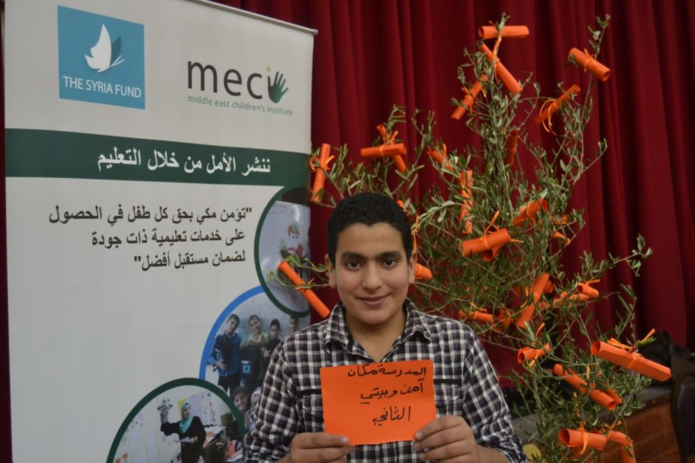 MECI-TSF 16.12.2018. A student is holding a message promoting Education.jpg