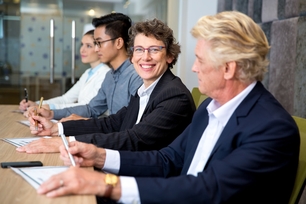 Smiling senior businesswoman sitting at meeting