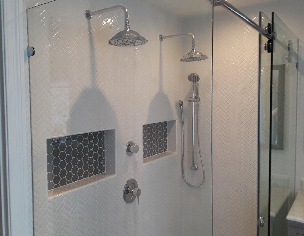 - Recessed shampoo nichesAccent tile in niche to match floorHoneycomb shower tileDouble rainhead showerheadsHerrinbone tile pattern on wall