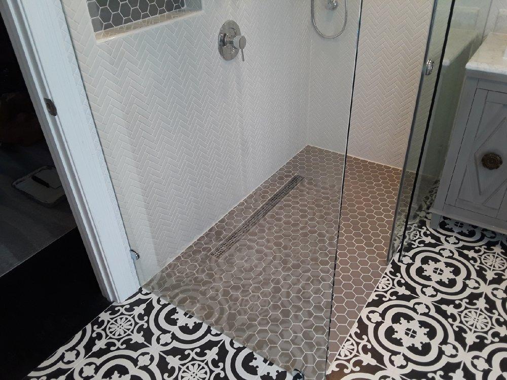- In-line shower drainCustom, virtually seamless, sliding shower door