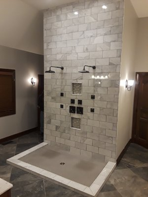 - 12x24 marble tile in showerRecessed niches with accent tileDouble rainhead showerheadsOil-rubbed bronze hardware24x24 floor tilesCustom glass shower door (not shown)