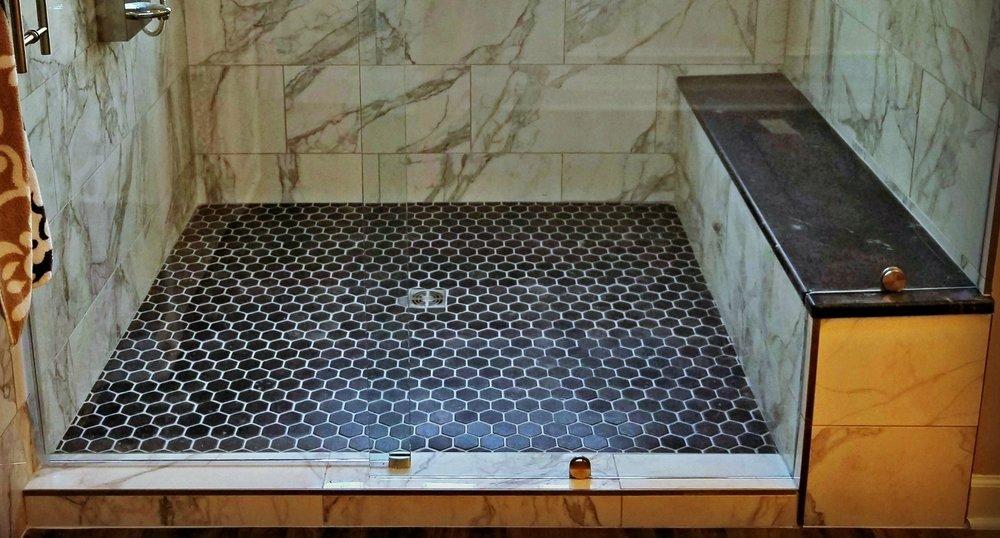 - Honeycomb tile on shower fllorCustom shower seatGranite on shower seat to match granite on vanity