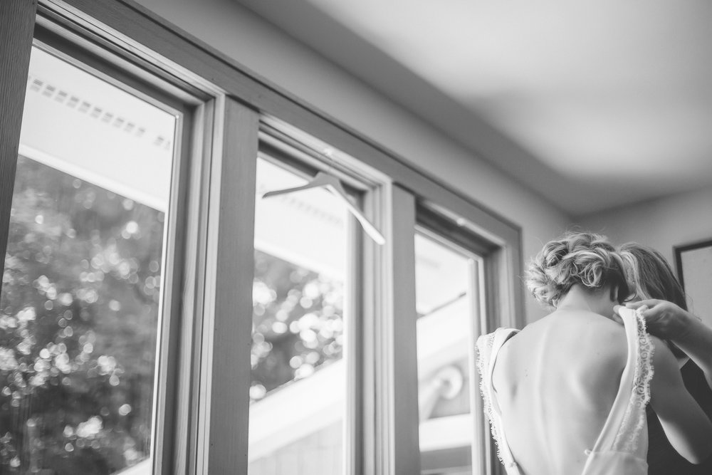 17 Minneapolis home backyard wedding bride putting on dress.jpg