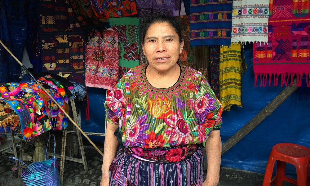 Business owner at the market in Chichicastenango selling vintage huipil and corte textiles