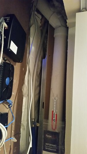 The piping is going down behind the wall, keeping the system monitor visible and the closet accessible