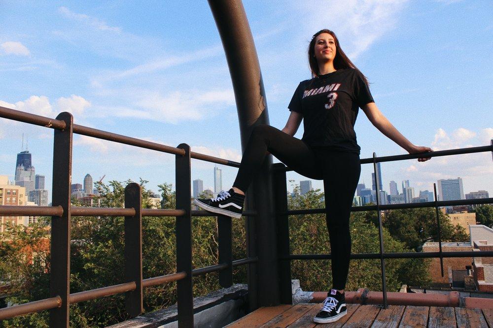 Amanda wears Miami Heat t-shirt,  @vtgindy ; leggings.  Adidas ; Sk8-Hi Slim Sneaker,  Vans .