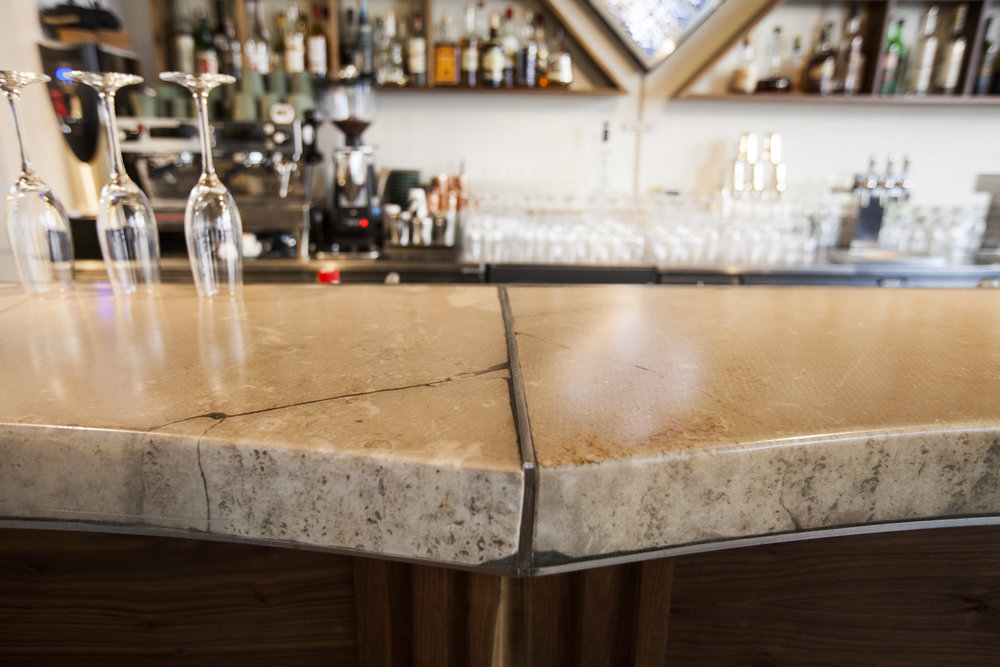 The bar top, a resin pour over slabs of sandstone, pieces saved from the Longnow Clock site in Texas.