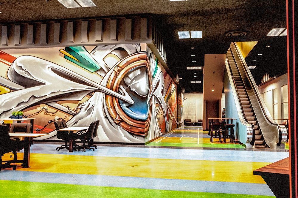 The first floor has hopscotch & shuffle board dyed into the striped, multi-colored floor; a sea of white, articulated seating and tables are found along the 120 ft. long graffiti mural by Sean Griffin (Griffin One).