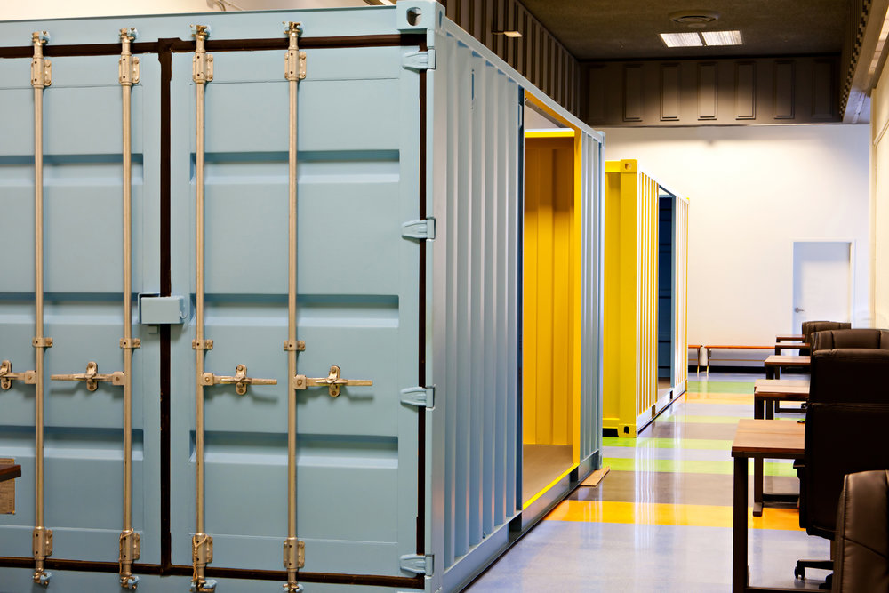Vibrant shipping container-meeting rooms line the large hallways.