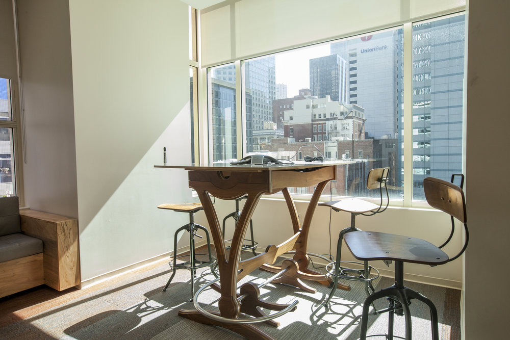 A standing height work table by the window allows multiple kinds of meetings in this sun light room.