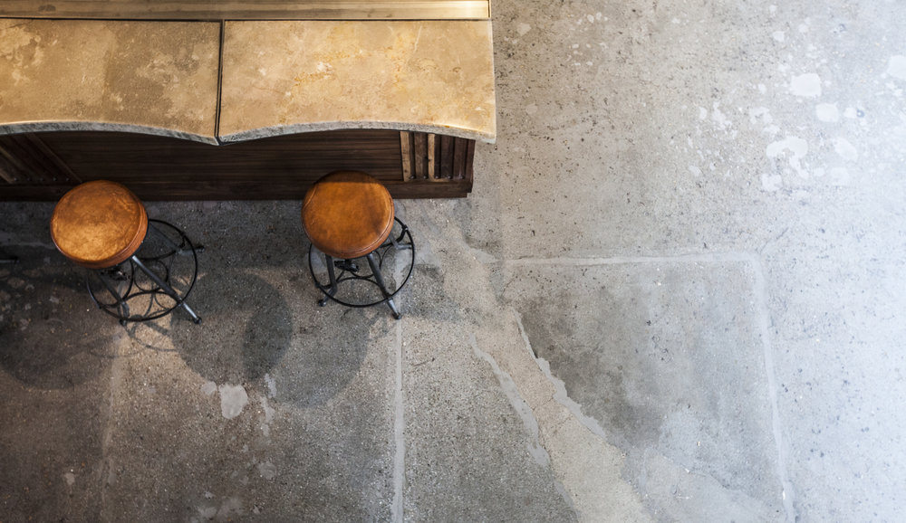 Complementing the floor original concrete floors that celebrate the space's history, a limestone bar top encased in resin. Bringing out the beautiful raw details of the stone, tt also provides a durable surface for the bar and cafe patrons.