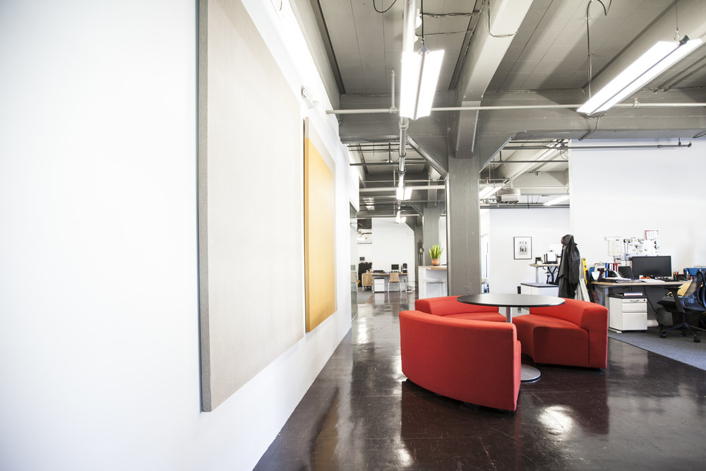 Simple seating and meeting areas throughout the space break up an open office.