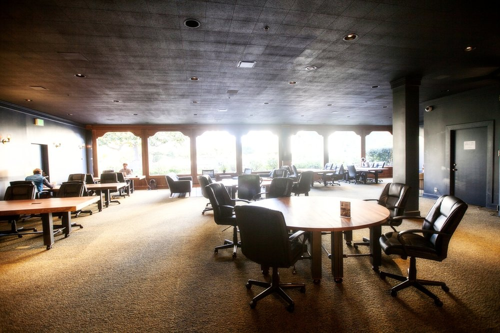 The second floor Co-Working is a dark wood, plush carpeting and light filled space with large work tables.  Tables designed & fabricated at BWC.