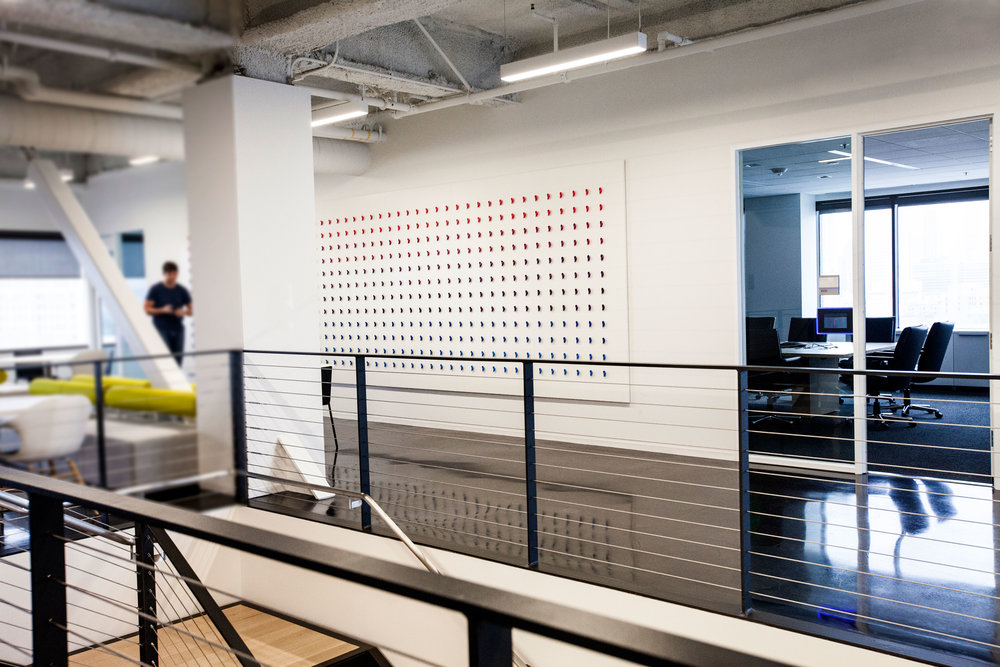 """Between conference rooms a color gradient wall grid of """"ears"""". A fun artistic nod to Dolby sound."""