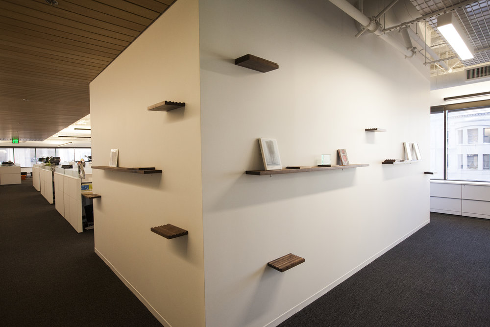 The shelves wrap the corners on both sides of this wall, and allow for fun display of their press materials and awards.