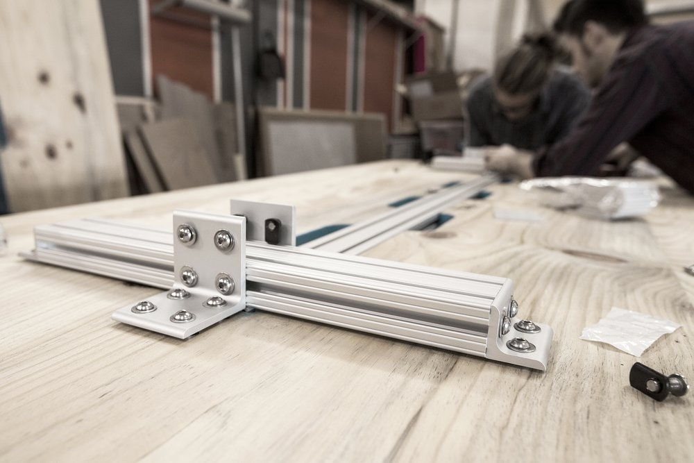Our fabricators working together to install the hardware on the underside of the machiche work tables.