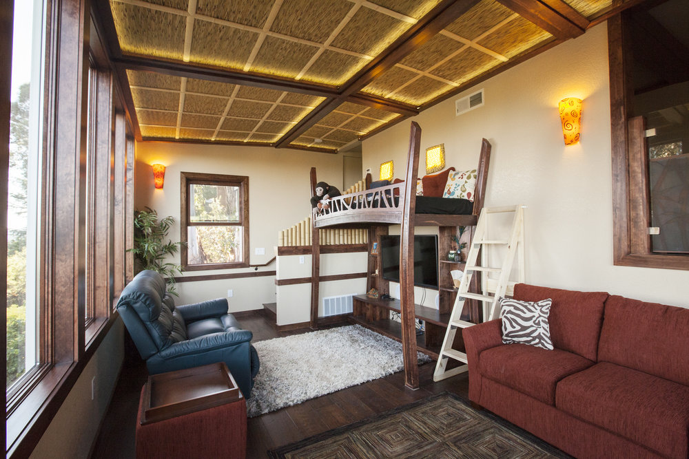 The new den has a 'kitchy' tropical theme with a thatch ceiling, dark wood flooring and window frames, a bamboo railing and fun loft bed.