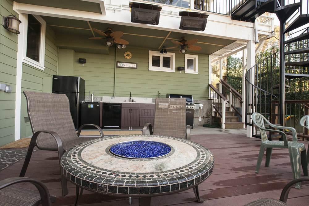 With all the additional space, a fun fire pit is added to the deck. In the background the spiral staircase and new outdoor kitchen can be seen.