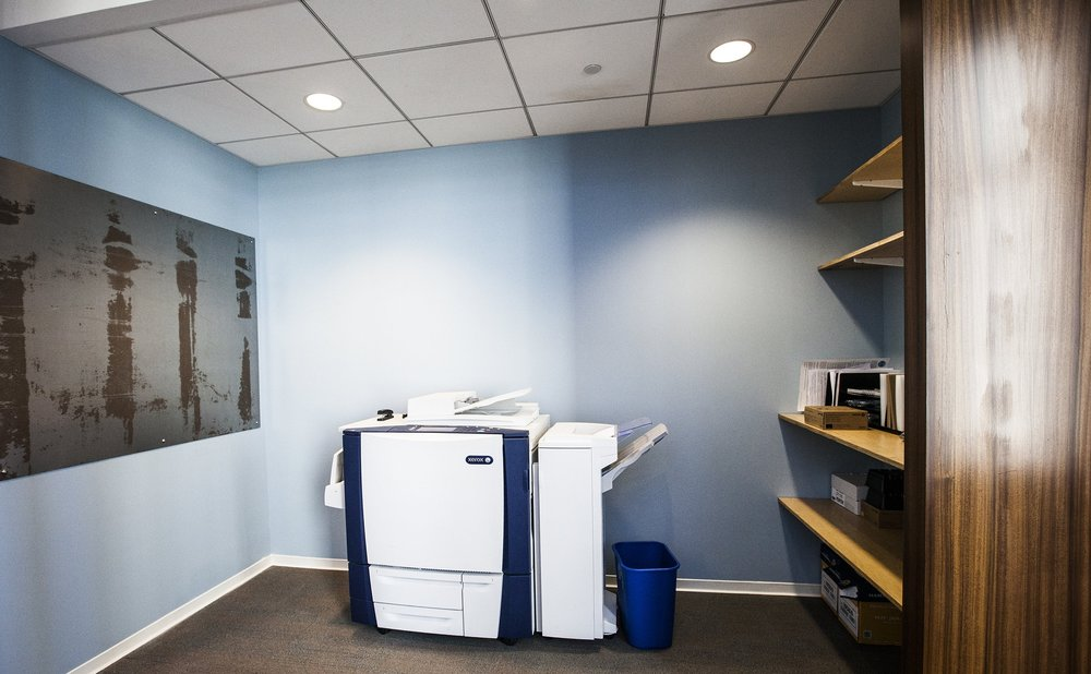 Even the tiny copy room has tones of the the office colors with wooden shelves, rusty metal and a sky blue wall.