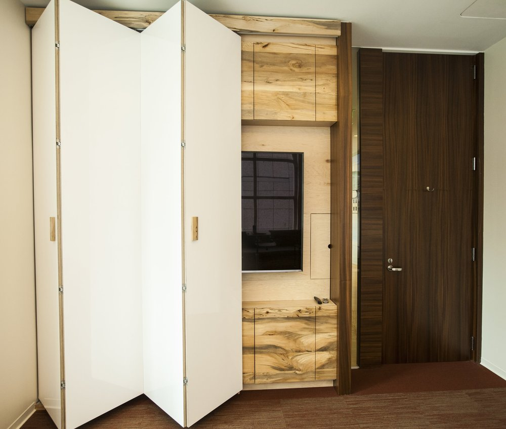 Accordion opening door reveals a beautiful sycamore paneled cabinet behind with storage and a large flat screen.
