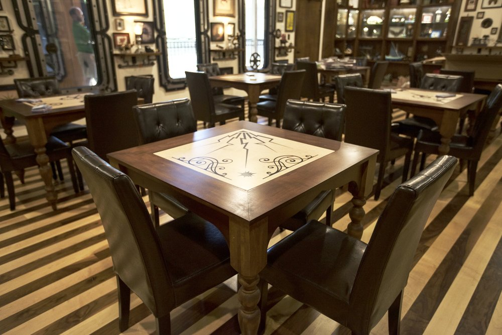Each table in the space has a unique center design done in wood and resin inlay.