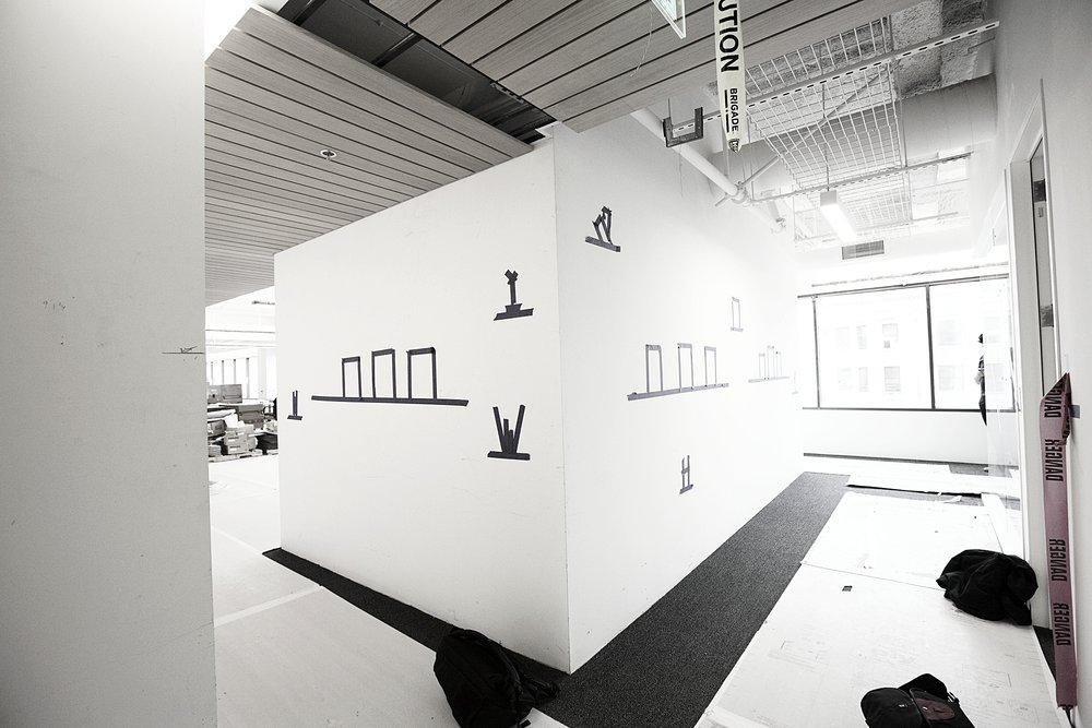 Laying out the display wall for the custom shelf installation.
