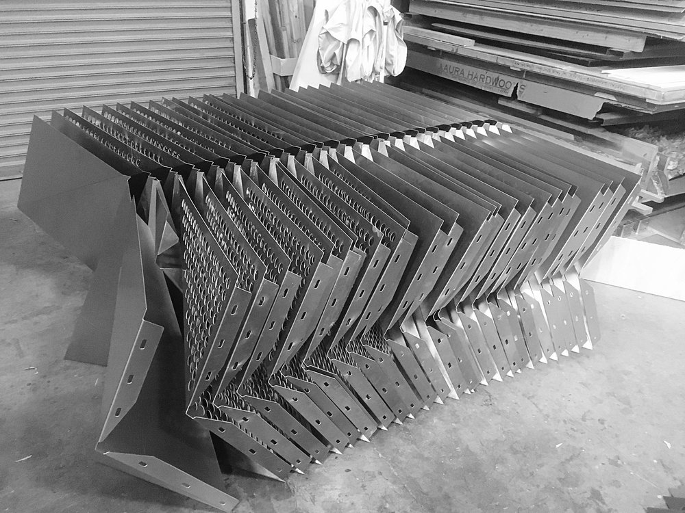 A stack of panels waits to be sent to the powder-coaters.