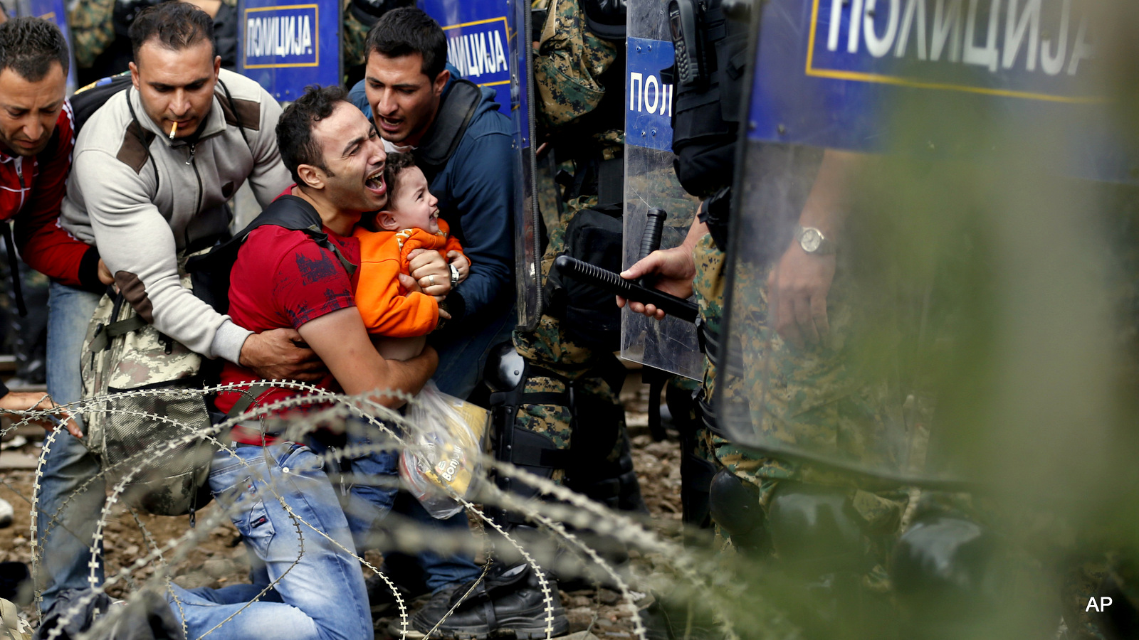 Migrant men help a fellow migrant man holding a boy as they are stuck between Macedonian riot police officers and migrants during a clash near the border train station of Idomeni, northern Greece, as they wait to be allowed by the Macedonian police to cross the border from Greece to Macedonia, Friday, Aug. 21, 2015. Macedonian special police forces have fired stun grenades to disperse thousands of migrants stuck on a no-man's land with Greece, a day after Macedonia declared a state of emergency on its borders to deal with a massive influx of migrants heading north to Europe. (AP Photo/Darko Vojinovic)