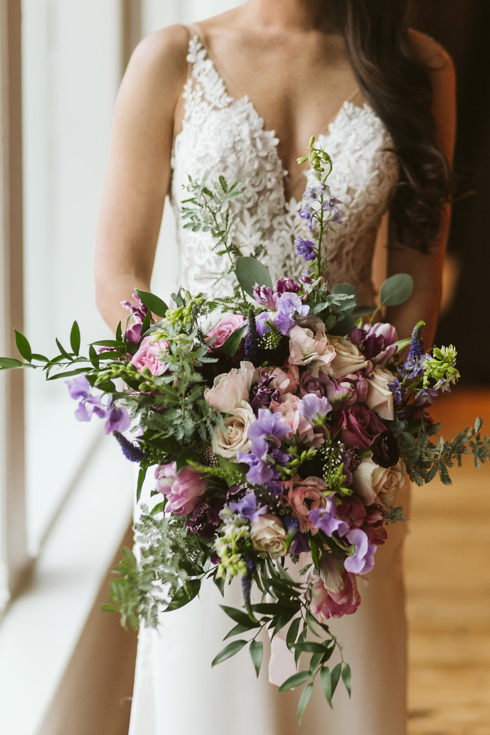 Textured Garden Bouquet with Slight Cascade  Style: garden, textured, woodland Details: sweet pea, veronica, ranunculus, larkspur, tulips, roses, mixed eucalyptus, silver dollar, ruscus greenery   {Photo courtesy of  Nick Allen Photo }
