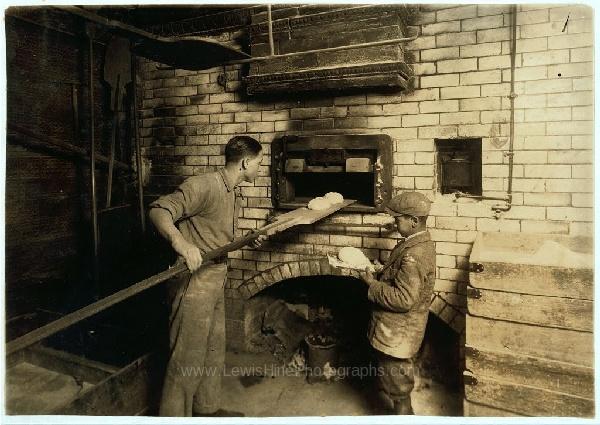Vicenzo Messina, 15 años, y su hermano Angelo, 11 años, horneando pan para su padre. 174 Salem Street. Vincenzo trabaja por las noches por ahora, de 5PM a 5AM, pero normalmente trabaja el turno matutino. Angelo ayuda mucho, atiende la tienda, apoya con el horneado. Cambridge, Massachusetts, febrero 1, 1917.