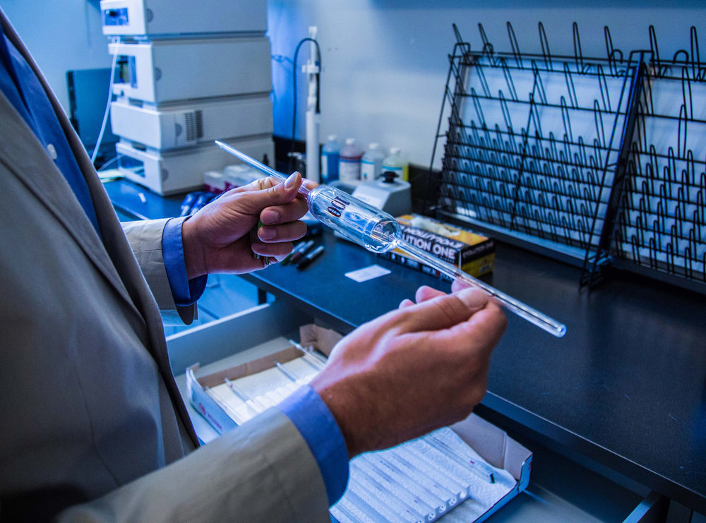 A GenCanna lab technician reviews a sample for quality.