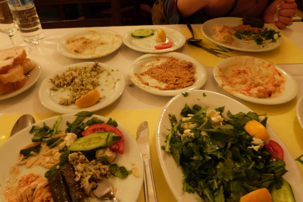 The Spread: (Clockwise from top left: Hummus, stuffed grape leaves (well, what was left of them), fried eggplant with yogurt and red pepper, arugula and beyaz peynir (white cheese) salad, whiting salad and chicken and walnut salad.)