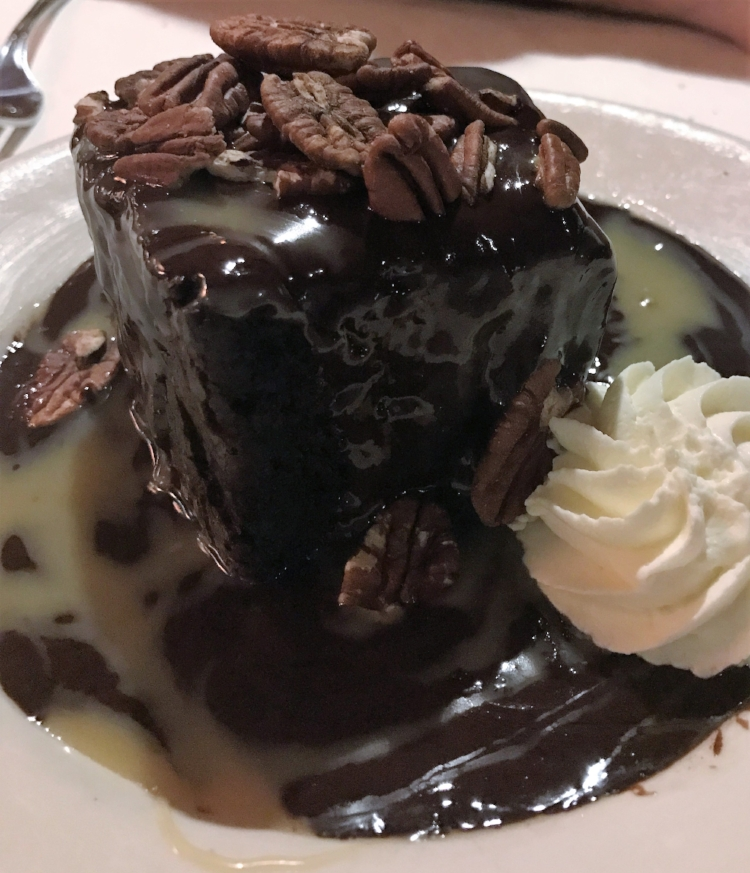 This decadent chocolate cake is covered in a warm chocolate sauce and finished with homemade whipped cream and roasted pecans.