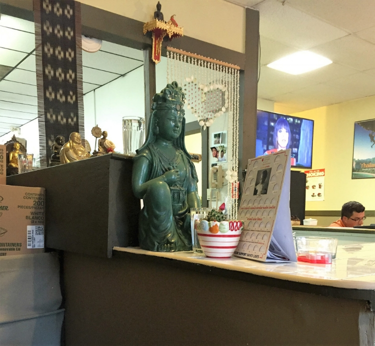 The décor is Spartan: Plain tables flank either side of a horseshoe-shaped center counter, where diners order food. A jade-colored Buddha statue sits on the counter next to cardboard boxes filled with Styrofoam takeout containers.