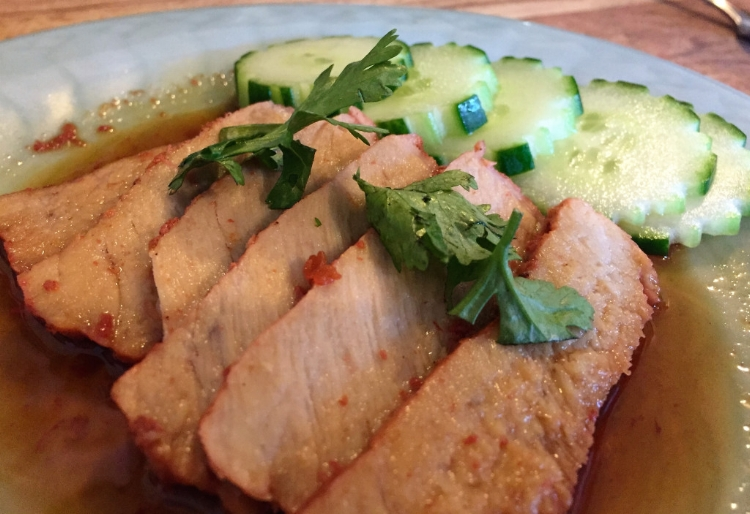An appetizer of oven-roasted spiced pork served with cucumber and cilantro.