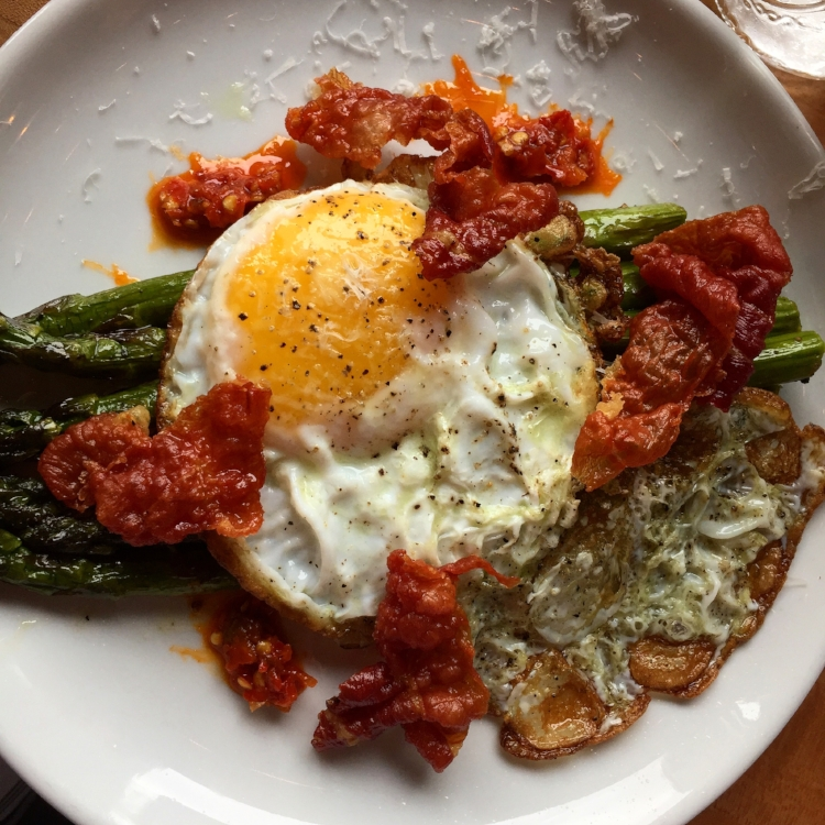 Roasted asparagus with a fried duck egg, crispy speck, shredded Grana Padano cheese and Calabrian chili from Apizza Regionale.