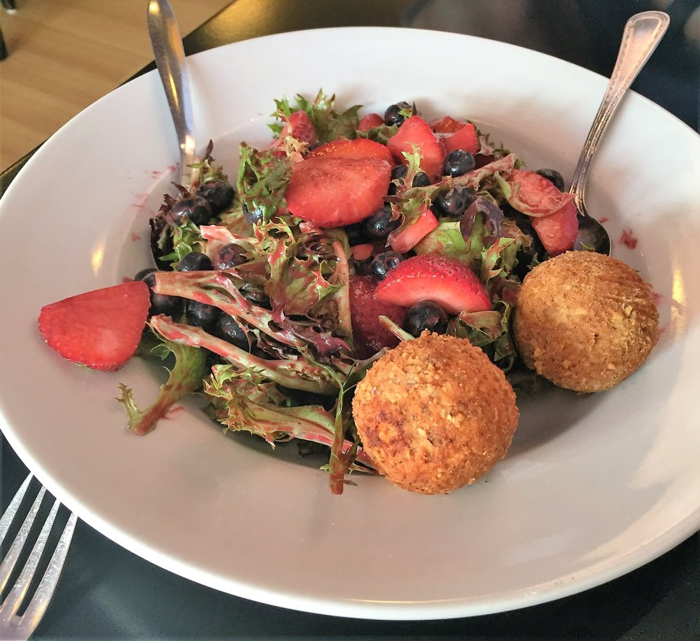 The salad combines crisp greens, fresh berries and warm, fried goat cheese.