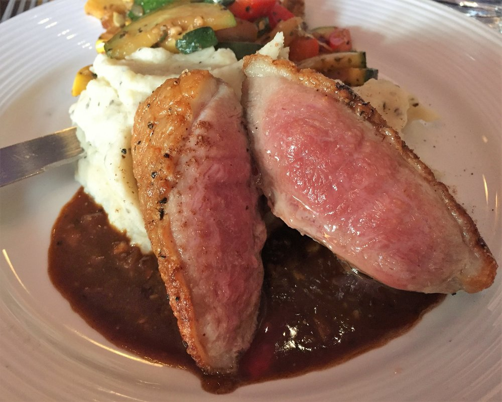 Seared duck breast, served medium-rare, served with hoisin pan sauce, mashed potatoes and summer vegetables.