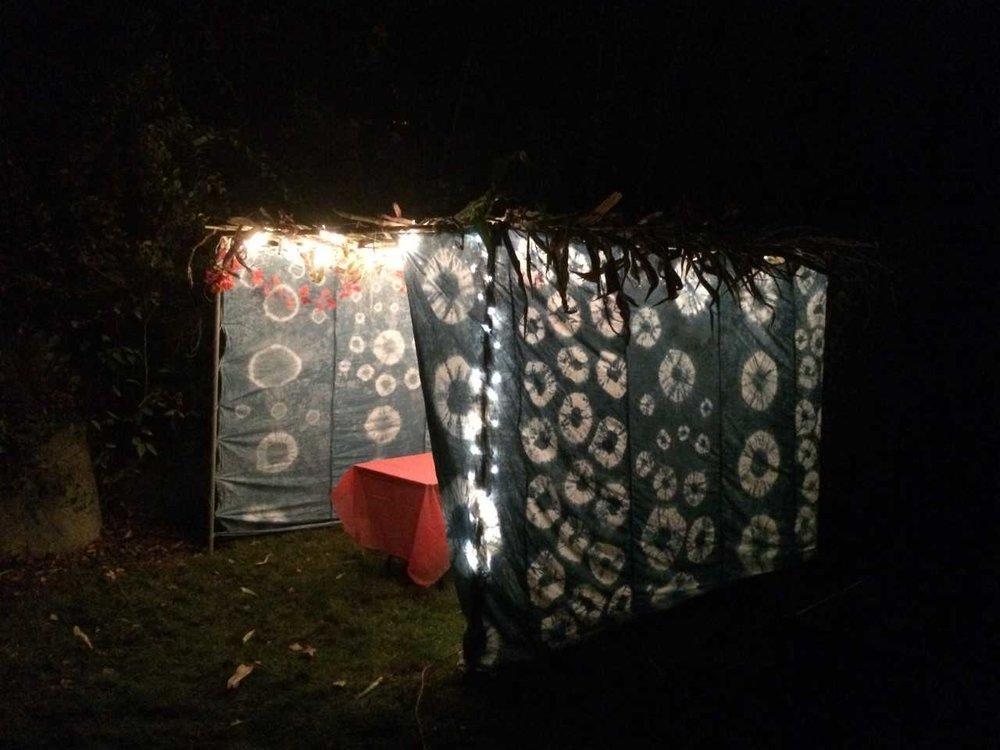 Indigo Sukkah, 2014, 25 yards of hand dyed indigo shibori cotton with twinkle lights, metal frame, and corn husks, 12'x6'x10'