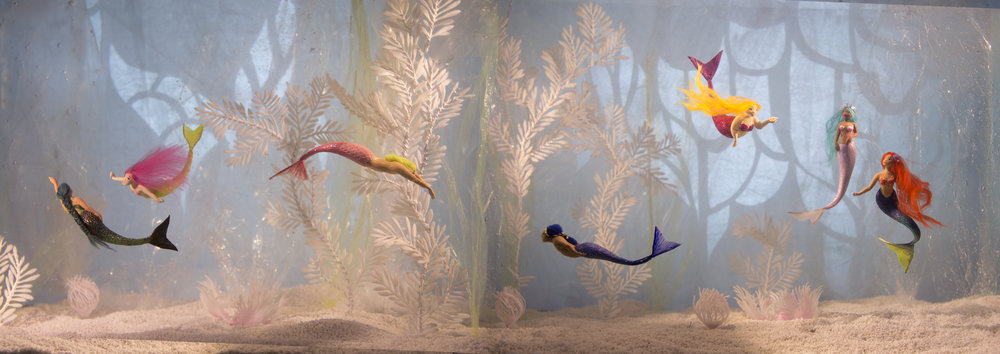 More tiny mermaid sculptures photographed in a fish tank.